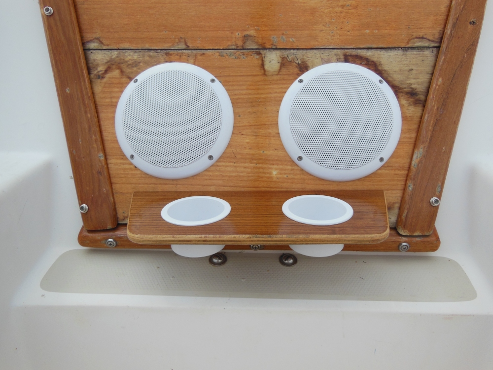 Waterproof speakers installed in the lower hatch board above drink holders