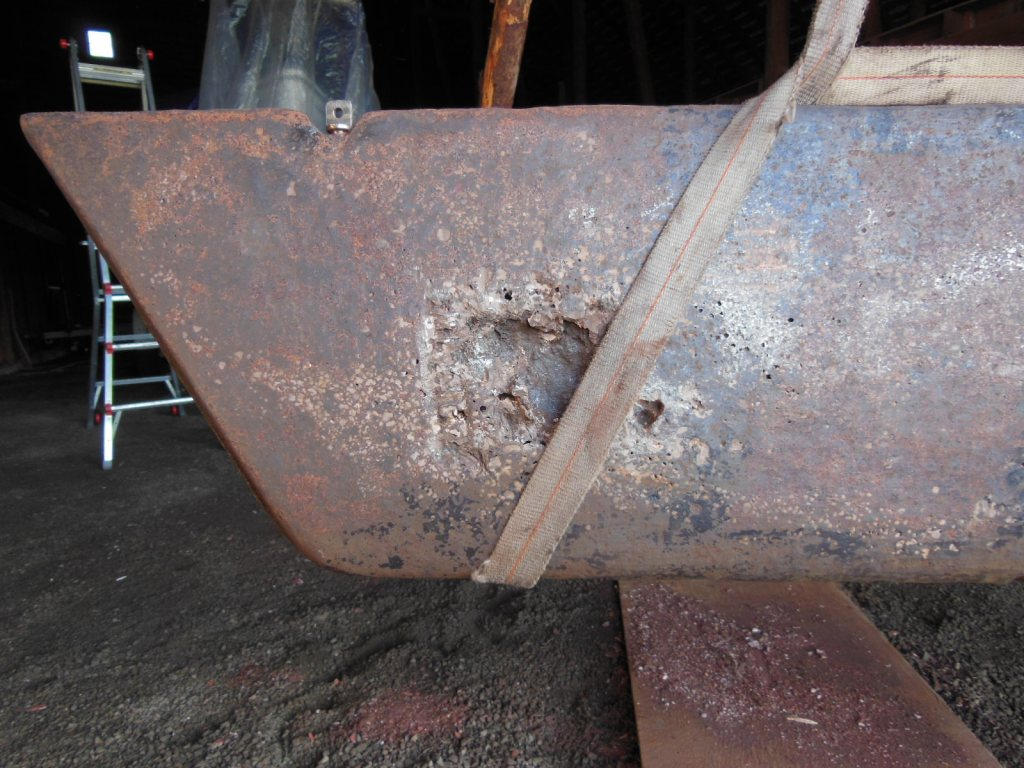 Large cavity uncovered during grinding. Note the zinc anode screw hole to the right of the strap.