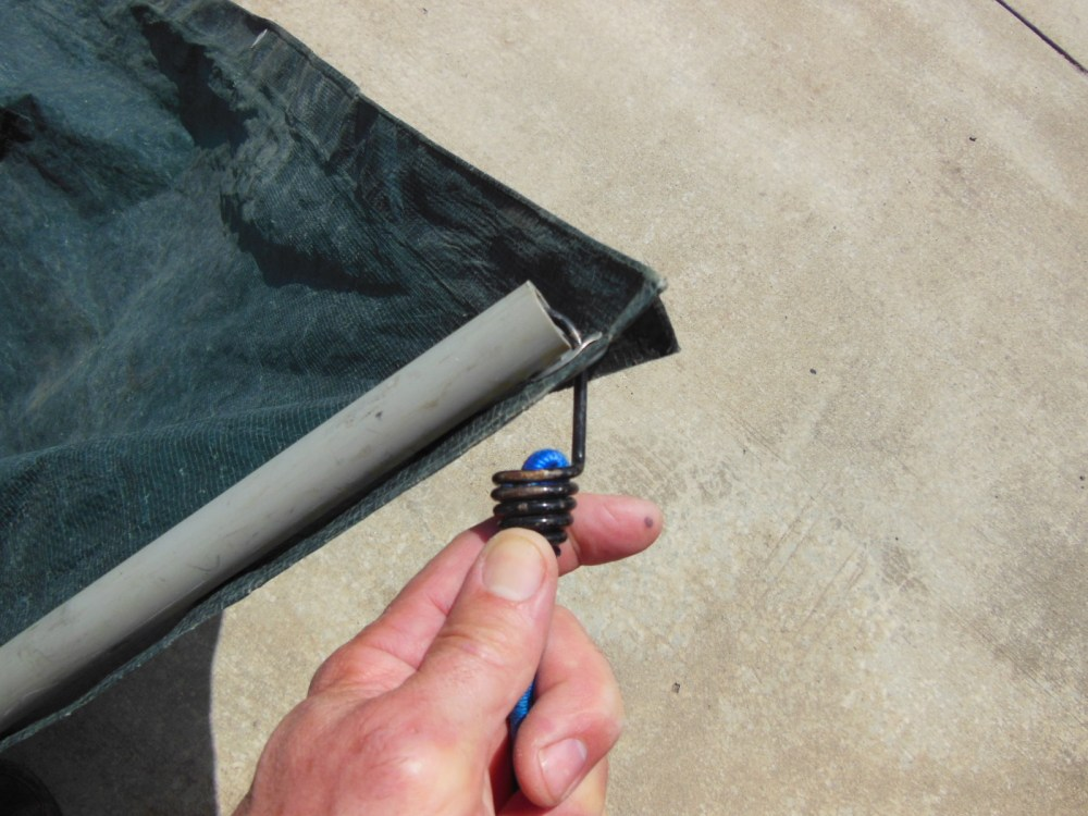 Hook each corner of the tarp to the ends of the pipe