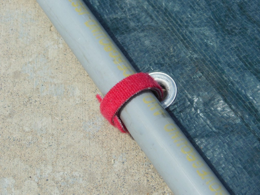 Lash the tarp to the pipes with hook-and-loop strips